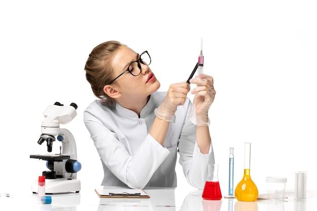 Medico femminile di vista frontale in vestito medico bianco che tiene iniezione su spazio bianco chiaro