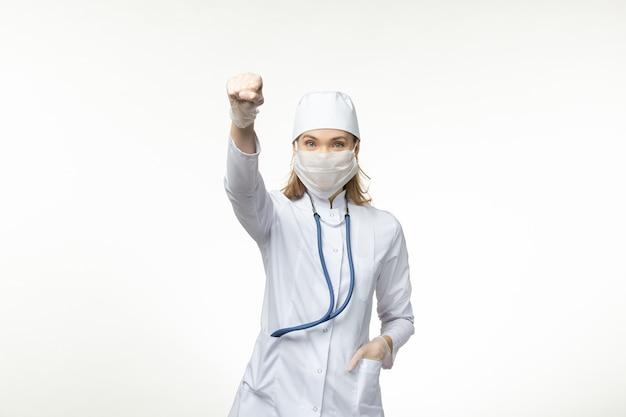 Dottoressa vista frontale in tuta medica bianca e maschera come protezione dal coronavirus sulla scrivania bianca covid - malattia pandemica