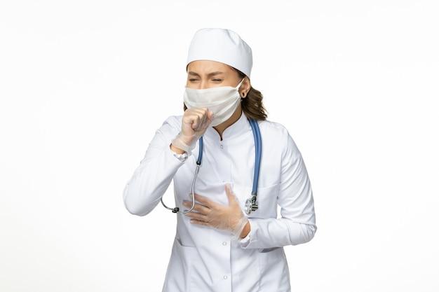 Medico femminile di vista frontale in vestito medico bianco e maschera che tossisce sulla medicina di malattia di malattia del virus della pandemia della parete bianca