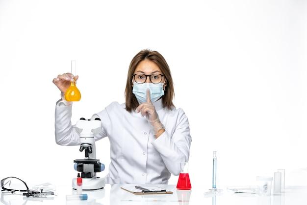 Dottoressa vista frontale in tuta medica bianca e maschera a causa del coronavirus che lavora con soluzioni su uno spazio bianco chiaro