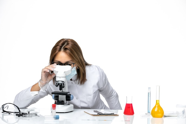 Front view female doctor in white medical suit and mask due to covid using microscope on white space
