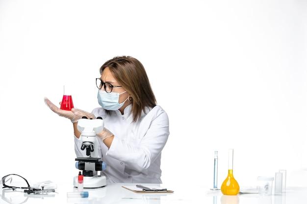 Medico femminile di vista frontale in vestito medico bianco e maschera dovuto covid che lavora con soluzioni sullo spazio bianco chiaro
