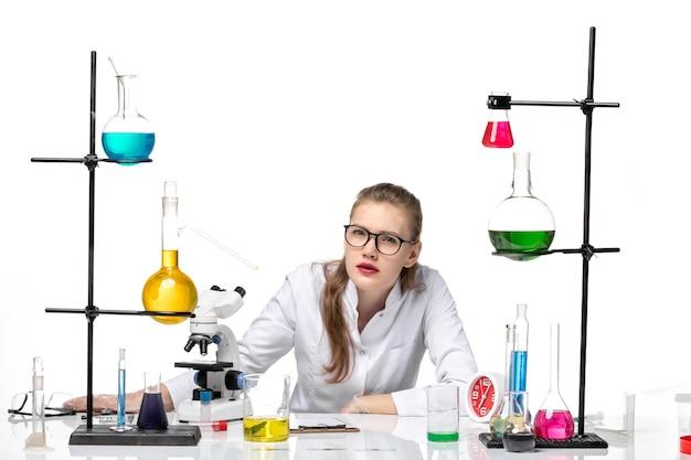 Medico femminile di vista frontale in vestito medico bianco che si siede con soluzioni su covid pandemia di chimica di salute del fondo bianco