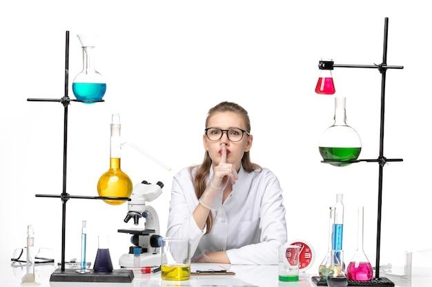 Medico femminile di vista frontale in vestito medico bianco che si siede con le soluzioni su chimica pandemic covid di salute del virus del fondo bianco