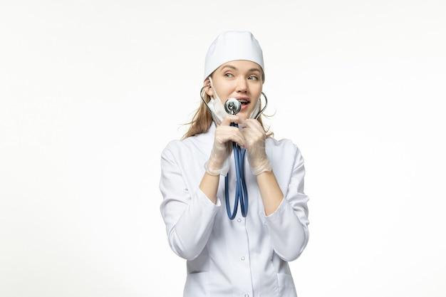 Medico femminile di vista frontale in vestito medico bianco facendo uso dello stetoscopio sulla malattia di covid-pandemia di malattia della scrivania bianca