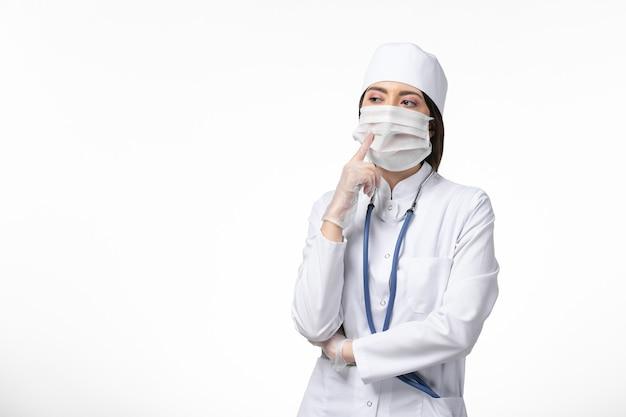 Medico femminile di vista frontale in vestito medico bianco con una maschera a causa del coronavirus che pensa profondamente alla malattia pandemica della malattia del muro bianco covid-