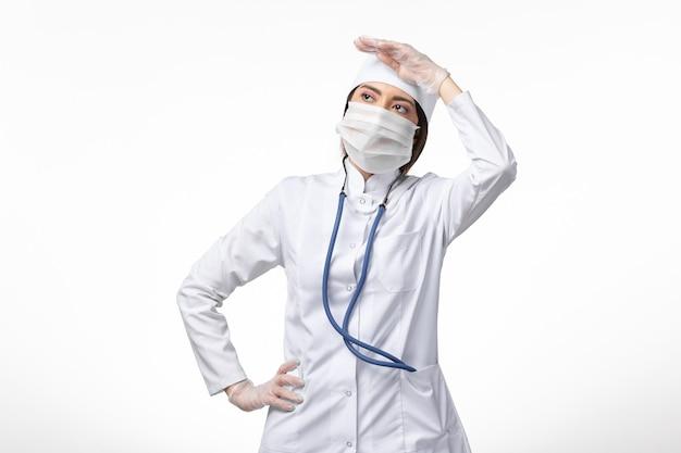 Medico femminile di vista frontale in vestito medico bianco con una maschera a causa di coronavirus sulla scrivania bianca malattia medicina virus pandemia covid-