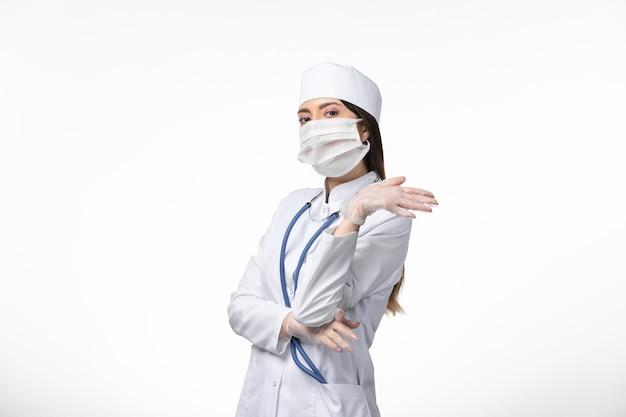 Medico femminile di vista frontale in vestito medico bianco con una maschera a causa del coronavirus sulla malattia di salute del muro bianco covid-