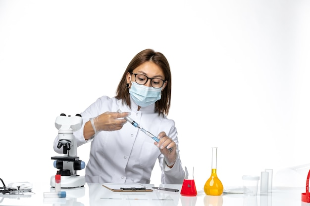 Medico femminile di vista frontale in vestito medico bianco con maschera a causa dell'iniezione della holding covid sullo spazio bianco-chiaro