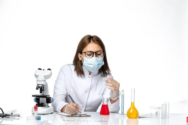 Medico femminile di vista frontale in vestito medico bianco con la mascherina dovuto covid che lavora su uno spazio bianco