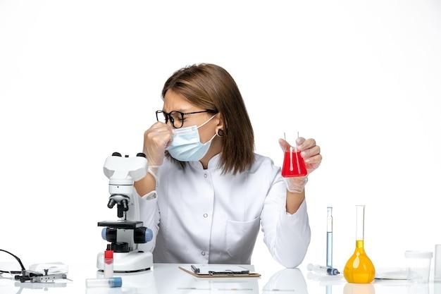 Dottoressa vista frontale in tuta medica bianca con maschera a causa di covid che lavora con soluzioni su spazio bianco chiaro