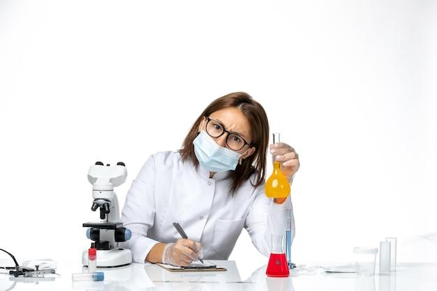 Medico femminile di vista frontale in vestito medico bianco con maschera a causa della scrittura covid su uno spazio bianco chiaro