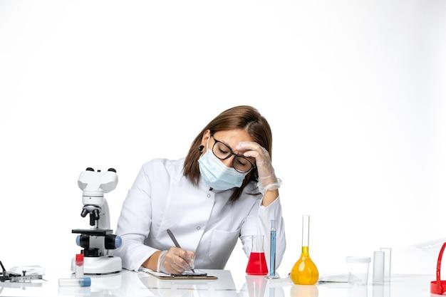 Medico femminile vista frontale in tuta medica bianca con maschera a causa di covid scrivendo qualcosa su uno spazio bianco chiaro