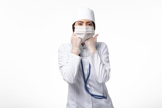 Medico femminile di vista frontale in vestito medico bianco con una maschera a causa della pandemia sulla medicina di salute di malattia del muro bianco covid