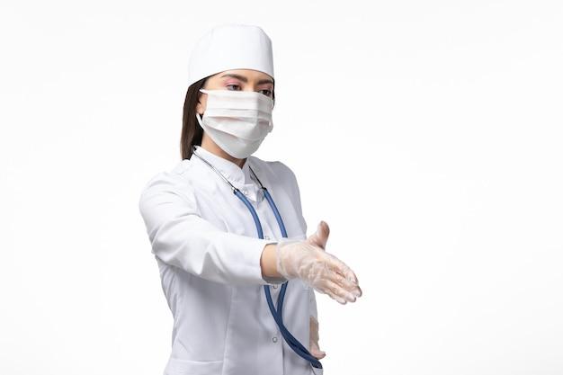 Dottoressa vista frontale in tuta medica sterile bianca con maschera a causa del coronavirus che stringe la mano sulla scrivania bianca malattia covid - virus della malattia pandemica
