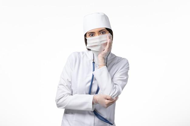 Dottoressa vista frontale in tuta medica sterile bianca con maschera a causa del pensiero del coronavirus sulla malattia da scrivania bianca covid - virus della malattia pandemica