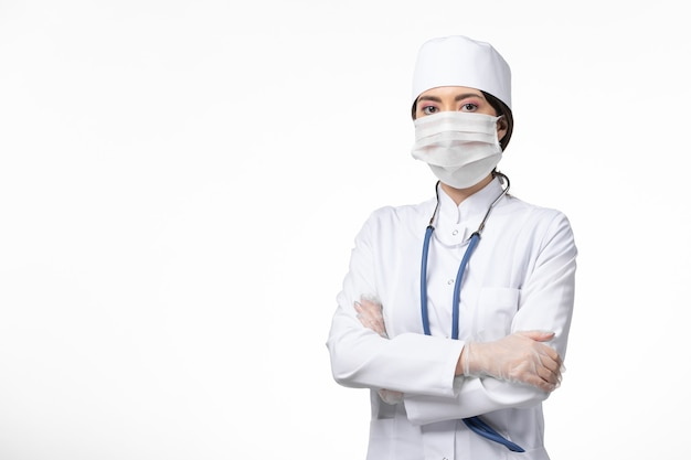 Front view female doctor in white sterile medical suit with mask due to covid- on white wall illness covid- pandemic disease