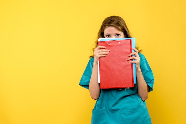 Front view of female doctor with analyzes on a yellow wall