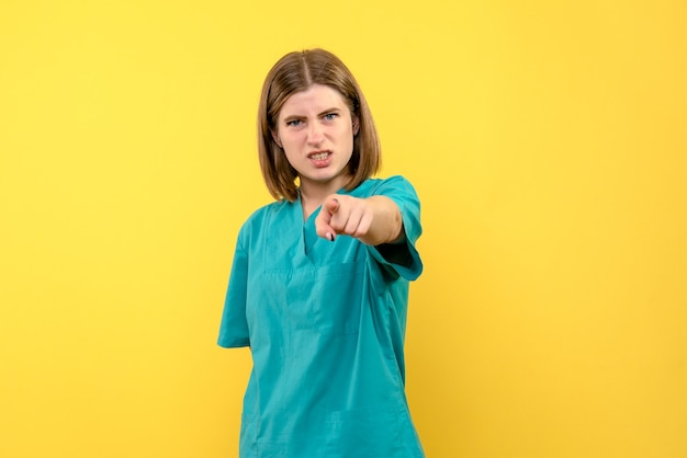 Front view female doctor with angry expression on yellow space