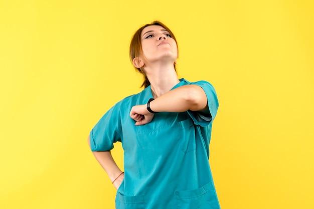 노란색 공간에 용감한 얼굴로 전면보기 여성 의사
