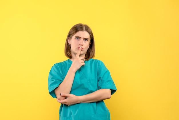 Medico femminile di vista frontale con espressione confusa sullo spazio giallo