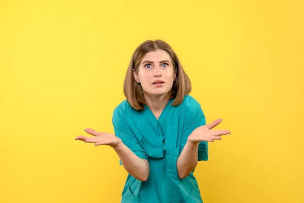 Front view female doctor with confused expression on yellow space