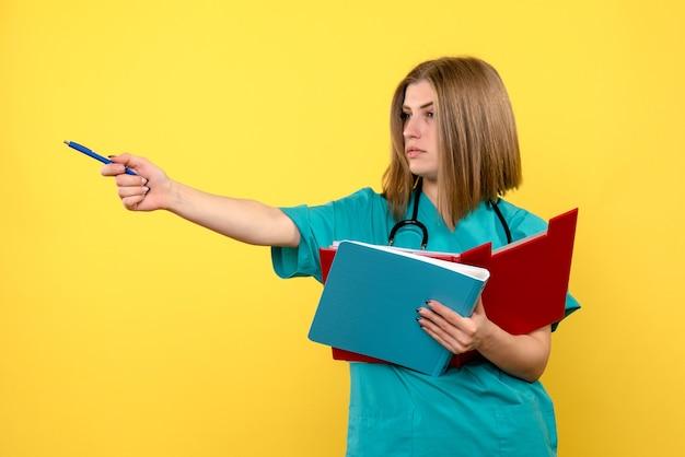 黄色のスペースにドキュメントと正面図の女性医師