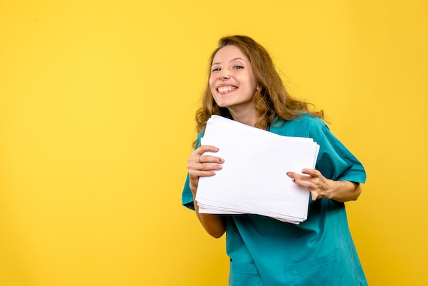 Front view female doctor with files on a yellow space