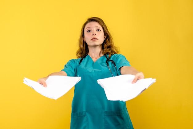 Medico femminile di vista frontale con file su spazio giallo
