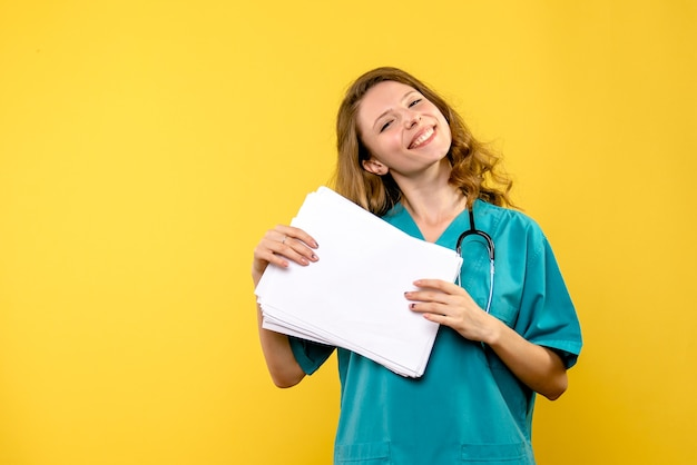 Front view female doctor with files on yellow space
