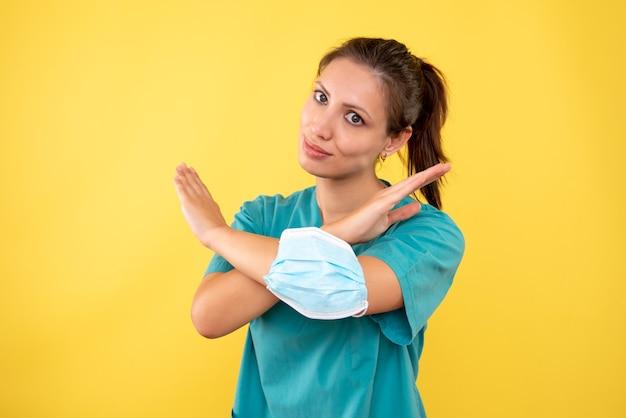 Вид спереди женщина-врач с маской на желтом фоне