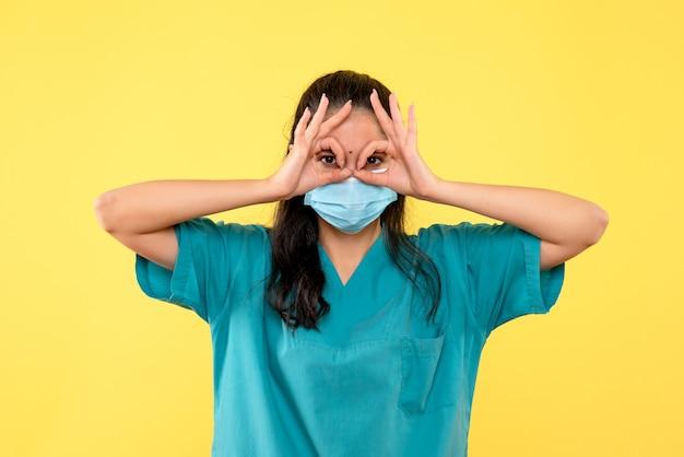 彼女の目の前にオーケーサインを置くマスクを持つ正面図の女性医師