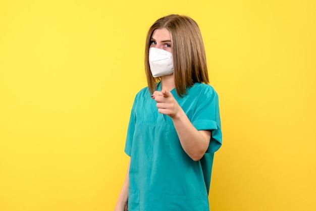 Vista frontale della dottoressa con maschera sulla parete gialla