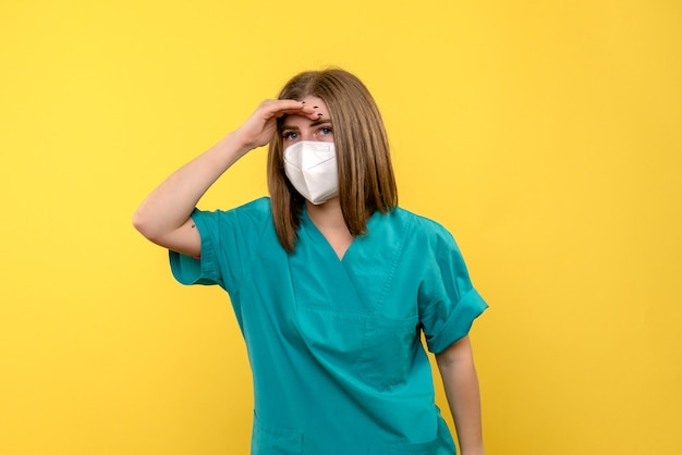 Front view of female doctor with mask on a yellow wall