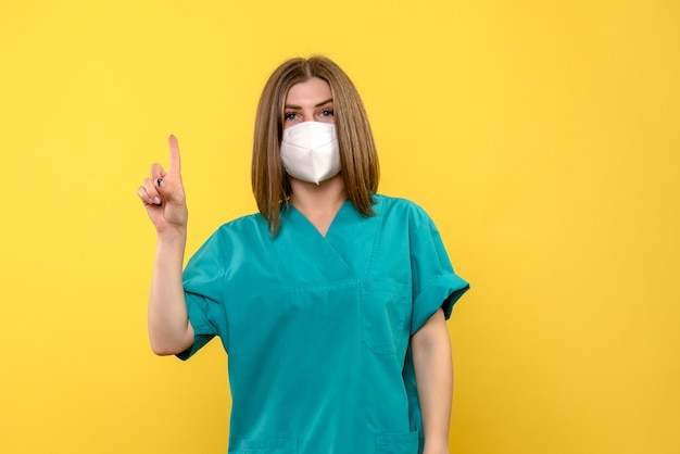 Front view of female doctor with mask on the yellow wall