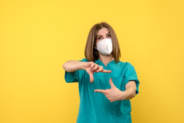 Front view of female doctor with mask on yellow wall