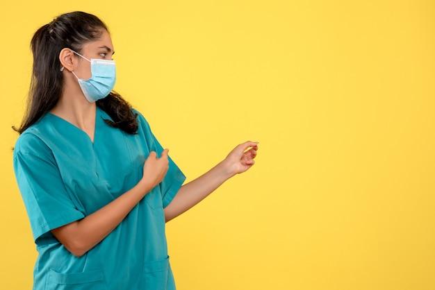 Medico femminile di vista frontale con mascherina medica che indica allo spazio giallo della copia
