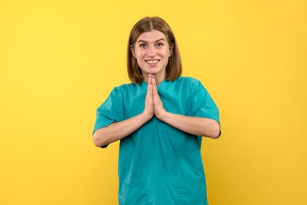 Vista frontale della dottoressa con espressione di preghiera sulla parete gialla