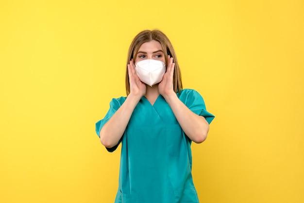 Vista frontale della dottoressa con maschera sterile sulla parete giallo chiaro