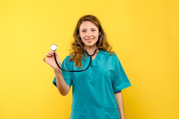 Medico femminile di vista frontale con lo stetoscopio sullo spazio giallo