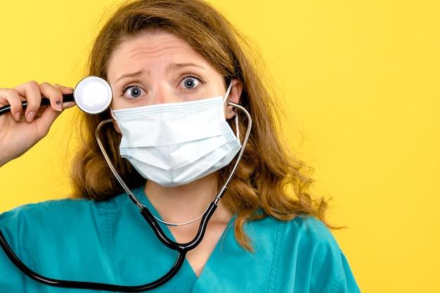 Front view female doctor with stethoscope on yellow space