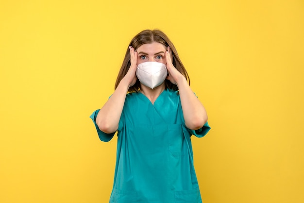 Front view of female doctor with stressed expression on yellow wall