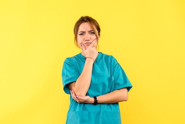 Vista frontale della dottoressa con la faccia pensante sulla parete gialla