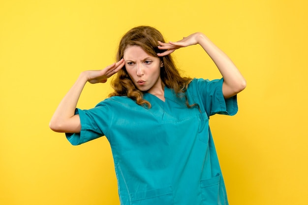 Front view of female doctor on a yellow wall
