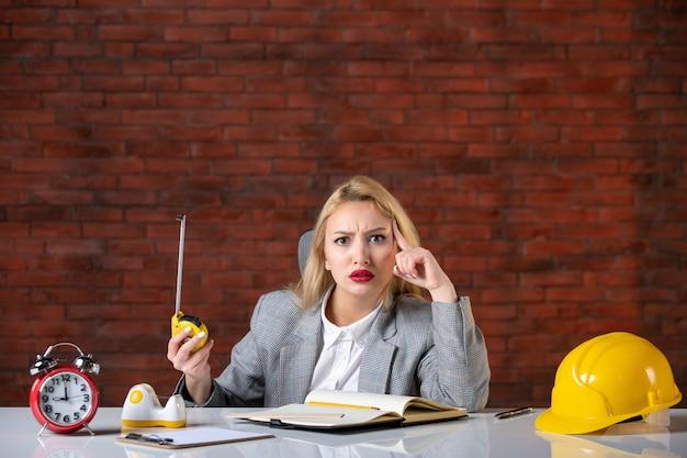 彼女の職場の後ろに座っている正面図の女性エンジニア