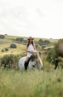 Front view of female farmer horseback riding