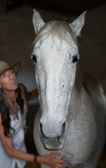 Front view of female farmer with her horse