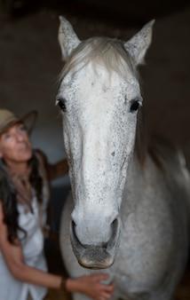 Vista frontale della donna contadina con il suo cavallo