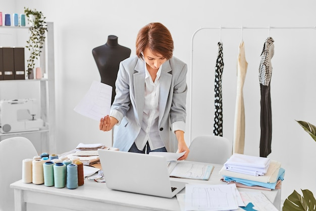 Front view of female fashion designer consulting clothing line plans in atelier
