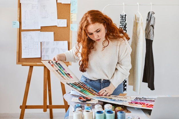 Front view of female fashion designer working with color palette in atelier